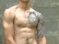 Kuuman aasialainen malliin tatuoinneilla tekee alaston kuvauksia outdoors