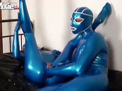 Kinky girl in latex fingers pussy trough the slit