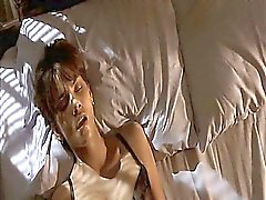 Halle Berry sitting on a couch as a guy pulls up her top to