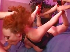 Bootylicious redhead in latex corset gets pounded in gang bang