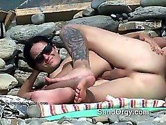 Chica monta polla en la playa de público en nude