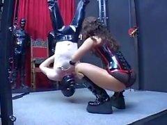 Senhora dominando seu escravo na frente de seus outros escravos