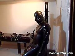 Horny slut gets in latex suit to suck