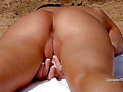 Hete blonde in zwarte bikini onthult haar enorme boezem op het strand
