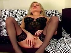 Blonde babe in lingerie and stiletto high heels masturbating on a couch