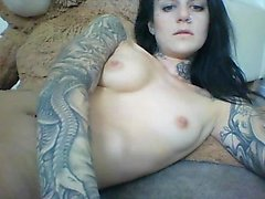Seductive tattooed brunette displays her lovely boobs on the webcam