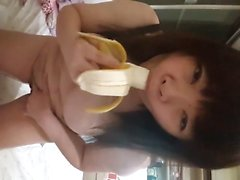Asian playing with a banana before jamming it in her pussy