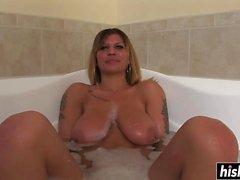 Tatuoitu tyttö rentouttaa kylpyammeessa