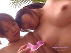 2 Asiatiska flickor stimulera sina bröstvårtor med leksaker på soffan