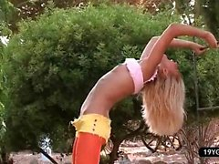 Sexy hot blond doing outdoor striptease show