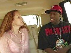 Sensuell tjej med långt rött hår gör avsugning för afro killen i bilen