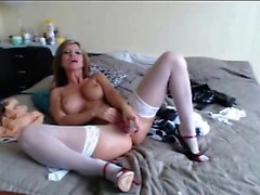 Elegant blonde milf in white stockings works her pussy on a