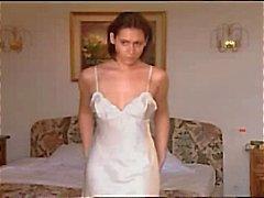 Brunette in witte satijnen nachtjapon masturbeert