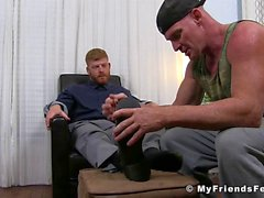 Inked ginger jerks off while his feet get worshiped by homo