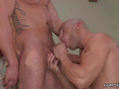 Ein muskulöser Glatzkopf, der von seinem Freund lutscht