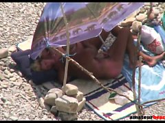 Handjob on candid beach with old nudist couple
