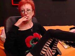 Gözlü sıcak kızıl bayan, bir sigarayı sever ve kaybeder
