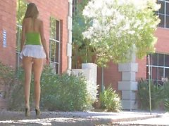 brunette is in the outdoors rubbing hard on her clitoris