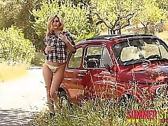 Summer strips from her plaid shirt down by the old car.
