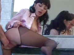 Hot, brunette MILF, in black stockings gets fucked in the kitchen