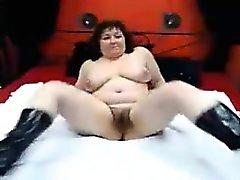 Busty mature dame en bottes noires révèle sa chatte poilue sur