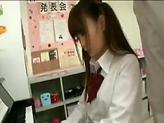 Pigtailed Oriental girl has her piano teacher fingering her