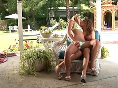 Two babes are outside using their fingers and licking off the juice