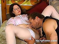 Stocking clad chick Lena Ramone gets her hairy natural pussy pleasured once more in this scene. Still lying down, her boyfriend spreads her thighs wide. He is still holding her pink comb. Her combs her pubes and slurps her clit, doing it simultaneously.