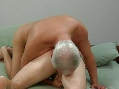 Older gay gives younger hunk a handjob on bed
