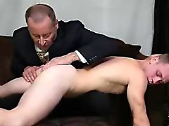 Older gay guy in suit spanking a young lad