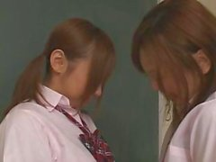 Two horny Asian school girls kissing and rubbing their tits in class