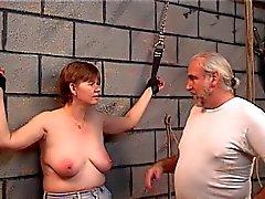 Sklaven bekommt Lederfesseln an ihren Handgelenken und Master setzt eine Peitsche auf die Titten