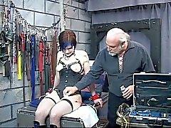 Brunette lindo de BDSM tatuado está conectada en el dispositivo la tortura eléctrico