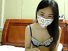 Nubile young brunette in a mask strips on webcam to show of
