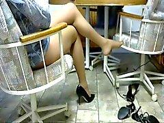 Die Beine in Strumpfhose und Pumpen