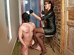 Busty brunette mistress in black tortures her masked slave