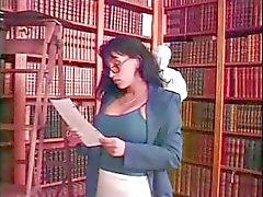 Ung blond skolflicka och busty brunett bibliotekarie spela med en strapon i biblioteket