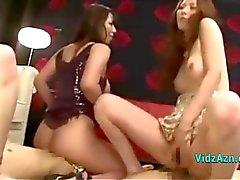 4 meninas asiáticas que montam no 2 homens Faces e galos no tapete A Roo Sentando