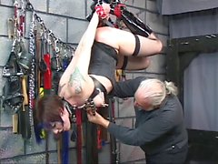Brunette in bondage geer is hung from the ceiling by her hands and feet