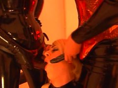 Two females in latex get strapon sucked by male in latex