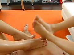 Arch gets these two brunette babes to give him a foot job after they play with each other