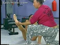 Beautiful slave is forced to crawl in a gym and is spanked on her ass and under her feet